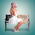 Classic fashion portrait american blond beauty sitting park bench wearing fashionable headscarf sunglasses white retro dress green Royalty Free Stock Photos