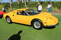 Classic ferrari sports car lineup side view yellow dino gt by in a and two lady onlookers focus on front end and fender Stock Images
