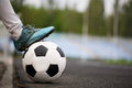 A classic football ball on an asphalted path background. Children training soccer. Healthy lifestyle. A ball on a grass. Royalty Free Stock Photo
