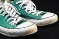 Classic green sneaker pair of worn out isolated on black background Royalty Free Stock Image