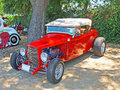Classic high boy roadster this is a red ford with a performance v engine custom paint job and chrome spoke wheels Stock Image