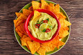 stock image of  Classic Homemade avocado hummus with olive oil, pita chips, lime, chilli, parsley on wooden background