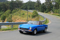 Classic blue italian sports car on downhill road Royalty Free Stock Photo