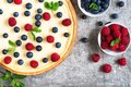 Classic New York cheesecake with fresh berries and mint on stone background, top view Royalty Free Stock Photo