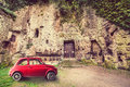 Classic old vintage red car. Archaeological area City of Sutri, Italy Royalty Free Stock Photo