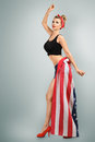 Classic pin up girl young blonde woman in skirt from flag style studio portrait Royalty Free Stock Images
