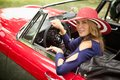 Classic red beauty wealthy attractive woman in her sports car looking at the camera and smiling Royalty Free Stock Image