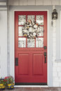 Classic red door to a white home with wreath and framed by gray detail patterned curtain is seen through the Royalty Free Stock Photos