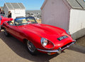Classic Red E Type Jaguar  Open Top Sports car parked on seafront promenade near beach huts. Royalty Free Stock Photo