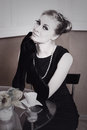 Classic retro styling woman in black dress and gloves at table Royalty Free Stock Photography