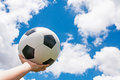 Classic soccer ball on hand with blue sky Royalty Free Stock Images