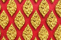 Classic Stone Carvings Thai Vintage Style Art of Golden Floral Seamless Pattern on Red Concrete Background Texture used as Beautif Royalty Free Stock Photo