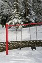 Classic swing set in a public park, red support stand and black rubber baby swing seats, snowy day