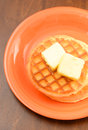 Classic waffles with butter two on orange plate and wood Royalty Free Stock Photography