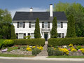 Classic white colonial style home a with hedges and nice roadside front garden Stock Photography