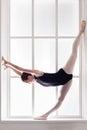 Classical Ballet dancer in split, ballerina at window sill