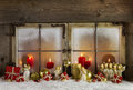 Classical christmas wooden window decoration with red candles an atmospheric and romantic snow angels and wood in white and golden Stock Image