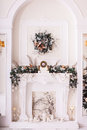 Classical fireplace decorated with tree branches. Vertical