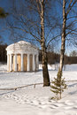 Classical rotunda with white columns in winter park Royalty Free Stock Photo