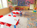 Classromm of kindergarten with tables and small red chairs Royalty Free Stock Photo
