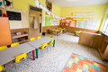 Classromm of kindergarten with tables and small yellow chairs Royalty Free Stock Photo