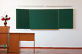 Classroom without student with wooden furniture and green blackboard Royalty Free Stock Images
