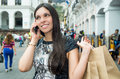 Classy attractive brunette wearing black white dress in urban environment carrying shopping bags while talking on phone Royalty Free Stock Photos