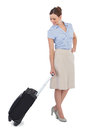 Classy businesswoman carrying suitcase against white background Stock Photos