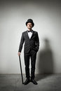 Classy gentleman with bowler hat and cane looking confidently at camera Royalty Free Stock Photo