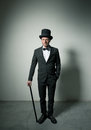 Classy gentleman with bowler hat and cane looking confidently at camera Royalty Free Stock Images