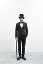 Classy gentleman smiling standing on white background and concrete floor in elegant suit with cane and bowler hat Stock Image