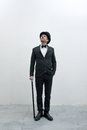 Classy gentleman standing on white background and concrete floor in elegant suit with cane and bowler hat looking up Royalty Free Stock Photos