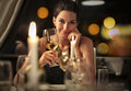 Classy woman drinking a glass of white wine at dinner Stock Images