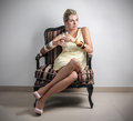 Classy woman sitting in an armchair Stock Photos