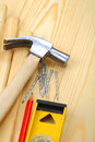 Claw hammer with nails and pencil on level Royalty Free Stock Photography