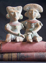 Clay aztec man woman sitting peacefully together top two classic books Stock Images