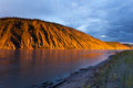 Clay cliff at yukon river near dawson city eroded bank territory canada glowing in orange light of summer sunset sun Stock Photo