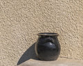 Clay jug dark brown on the background wall Stock Image