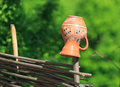 Clay jug on wooden fence in sunny day Stock Images
