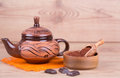 Clay teapot with chocolate on a wooden background Stock Images