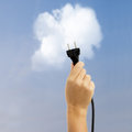 Clean alternative energy concept hand holding electric plug on blue sky with cloud background Stock Image