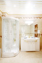 Clean bathroom with shower cabin and sink with mirror in classic style Stock Image