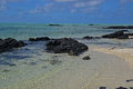 The clean clear transparent sea water off Ile aux Cerfs Mauritius with emerged black rocks and visible sandy beach