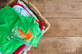 Clean unironed summer clothes in a laundry basket washed with fresh fragrance stacked wicker with bright green shirt on top Royalty Free Stock Photography