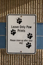 Clean up after dog sign black and white with paw prints on it asking owners to their dogs attached to a cement wall Stock Image