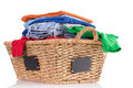Clean washed fresh clothing in a wicker basket pile of colorful rustic woven with blank labels on the sides ready to be ironed low Royalty Free Stock Images