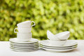 Clean white dishes cups white tablecloth green background Royalty Free Stock Photos