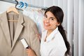 Cleaner in laundry shop with adhesive roller female removing lint from clothes Royalty Free Stock Photo