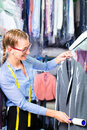 Cleaner in laundry shop checking clean clothes female removing lint with roller Stock Image