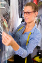 Cleaner in laundry shop checking clean clothes female or textile dry cleaning next to garment bags Royalty Free Stock Photography